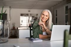 Happy senior fashionable woman. Portrait of happy senior woman holding eyeglasses and looking at camera at home. Successful old lady laughing and working at home royalty free stock image