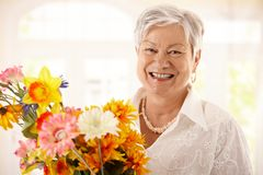 Portrait of happy senior woman holding flowers