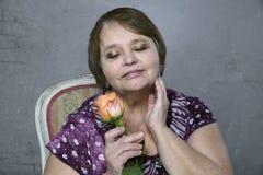 Portrait of happy senior woman holding orange rose Royalty Free Stock Image