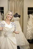 Portrait of a happy senior woman holding wedding gown in bridal store Royalty Free Stock Photography