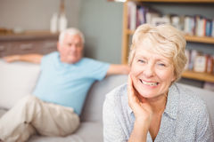 Portrait of happy senior woman with husband at home. Portrait of happy senior women with husband sitting in living room at home Stock Image