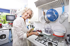 Portrait of happy senior woman preparing food in domestic kitchen Stock Images
