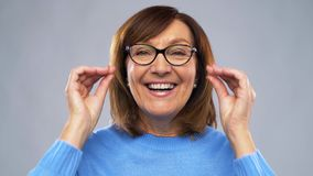 Portrait of happy senior woman putting glasses on stock video footage