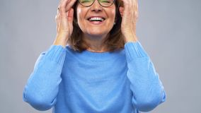 Portrait of happy senior woman putting glasses on stock footage