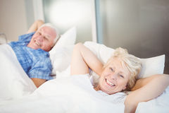 Portrait of happy senior woman relaxing besides man on bed Royalty Free Stock Photography