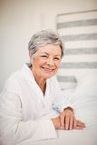Portrait of happy senior woman sitting on bed Royalty Free Stock Photo