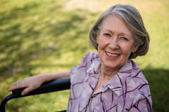 Portrait of happy senior woman sitting on wheelchair at yard Stock Photos