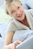 Portrait of happy senior woman smiling at home Royalty Free Stock Images