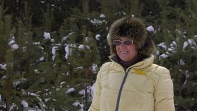 Portrait happy senior woman looking into camera during walking in winter forest stock footage