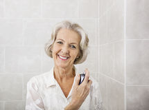 Portrait of happy senior woman spraying perfume in bathroom Royalty Free Stock Image