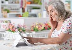 Woman  using digital tablet. Portrait of a happy senior woman using digital tablet Stock Images