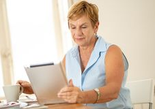 Portrait of a happy senior woman using electronic tablet at home. Portrait of a beautiful smiling mature woman using digital tablet while having breakfast and Royalty Free Stock Photo