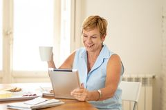 Portrait of a happy senior woman using electronic tablet at home. Portrait of a beautiful smiling mature woman using digital tablet while having breakfast and Stock Image