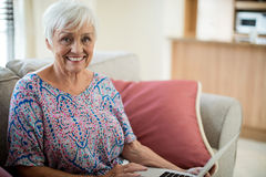 Portrait of happy senior woman using laptop in living room Stock Photos