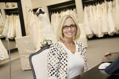 Portrait of a happy senior woman wearing eyeglasses sitting in bridal store Stock Photos