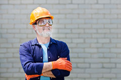 Portrait of happy seniorman with hard hat Posing with crossed ar Stock Photo