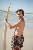 Portrait of happy shirtless man holding surfboard at beach Royalty Free Stock Photos
