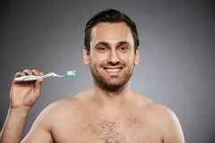 Portrait of a happy shirtless man holding toothbrush. With a toothpaste isolated over gray background Stock Photos