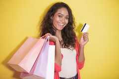 Happy shopaholic with shopping bag and credit card. Portrait of happy shopaholic with shopping bag and credit card on yellow background Royalty Free Stock Photo