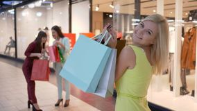 Portrait happy shopper girl with packages into hands on background of girlfriends near fashion store in season of stock video footage