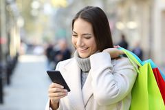 Shopper using a smart phone holding shopping bags. Portrait of a happy shopper using a smart phone holding shopping bags on the street in winter Royalty Free Stock Images