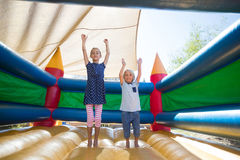 Portrait of happy siblings with arms raised jumping on bouncy castle. At playground royalty free stock photo
