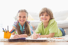 Portrait of happy siblings drawing while lying on rug Royalty Free Stock Photos