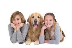 Portrait of happy siblings lying on the floor with their dog Stock Images