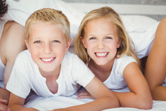 Portrait of happy siblings resting on bed Stock Photos