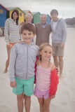 Portrait of happy siblings standing with parents in background Stock Images
