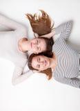 Portrait of happy sisters lying on the floor Stock Photo