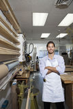 Portrait of a happy skilled worker standing with arms crossed in workshop Stock Images