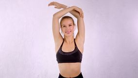 Portrait of happy slim fit young girl with fresh skin making stretch body looking at camera