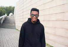 Portrait happy smiling african man in black hoodie, sunglasses on city street over gray brick wall royalty free stock photo