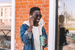 Portrait happy smiling african man calling on smartphone with coffee cup walking on city street over brick wall royalty free stock photo