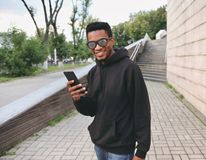 Portrait happy smiling african man with phone in black hoodie, sunglasses stock photos