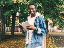 Portrait happy smiling african man reading book in autumn royalty free stock photo