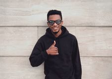 Portrait happy smiling african man showing thumbs up wearing black hoodie on city street over gray brick wall stock images