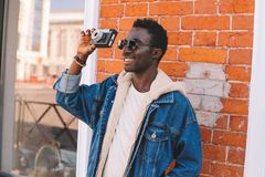 Portrait happy smiling african man with vintage film camera taking picture walking on city street over brick wall royalty free stock image
