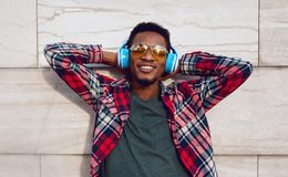 Portrait happy smiling african man with wireless headphones enjoying listening to music in city on gray wall background royalty free stock image