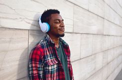 Portrait happy smiling african man in wireless headphones enjoying listening to music on city street over gray wall stock photo