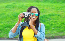 Portrait happy smiling african woman with retro vintage camera Stock Photos