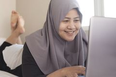 Happy Muslim Woman Working with Laptop in Her Bedroom. Portrait of happy smiling Asian muslim woman working with laptop in her bedroom, casual modern lifestyle royalty free stock photography