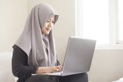 Happy Muslim Woman Working with Laptop in Her Bedroom royalty free stock images