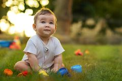 Portrait of Happy Smiling Baby Boy Playing with Toys. In Backyard Garden in Summer Season at Sunset stock images