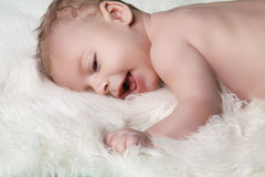 Portrait of happy smiling baby boy on white fur coat background Royalty Free Stock Images