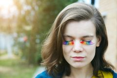 Happy smiling beautiful young woman with rainbow lgbtq eyelashes. Portrait of happy smiling beautiful young woman with rainbow lgbtq eyelashes royalty free stock photo