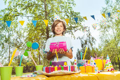 Portrait of happy smiling boy with birthday gift. Happy young boy in birthday hat holding box in pink gift wrapping, standing next to the table with B-day cake Royalty Free Stock Photos