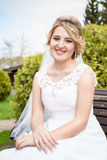 Portrait of happy smiling bride sitting on bench at park Royalty Free Stock Photography