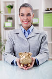 Portrait of happy smiling business woman, holding gold piggy ban Royalty Free Stock Photo